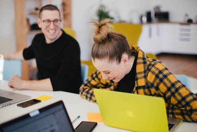Dos personas ríen en una oficina