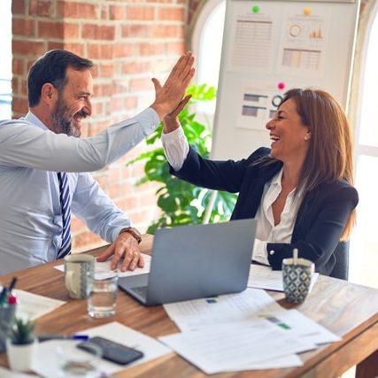 Hombre y mujer sonriendo tras un éxito